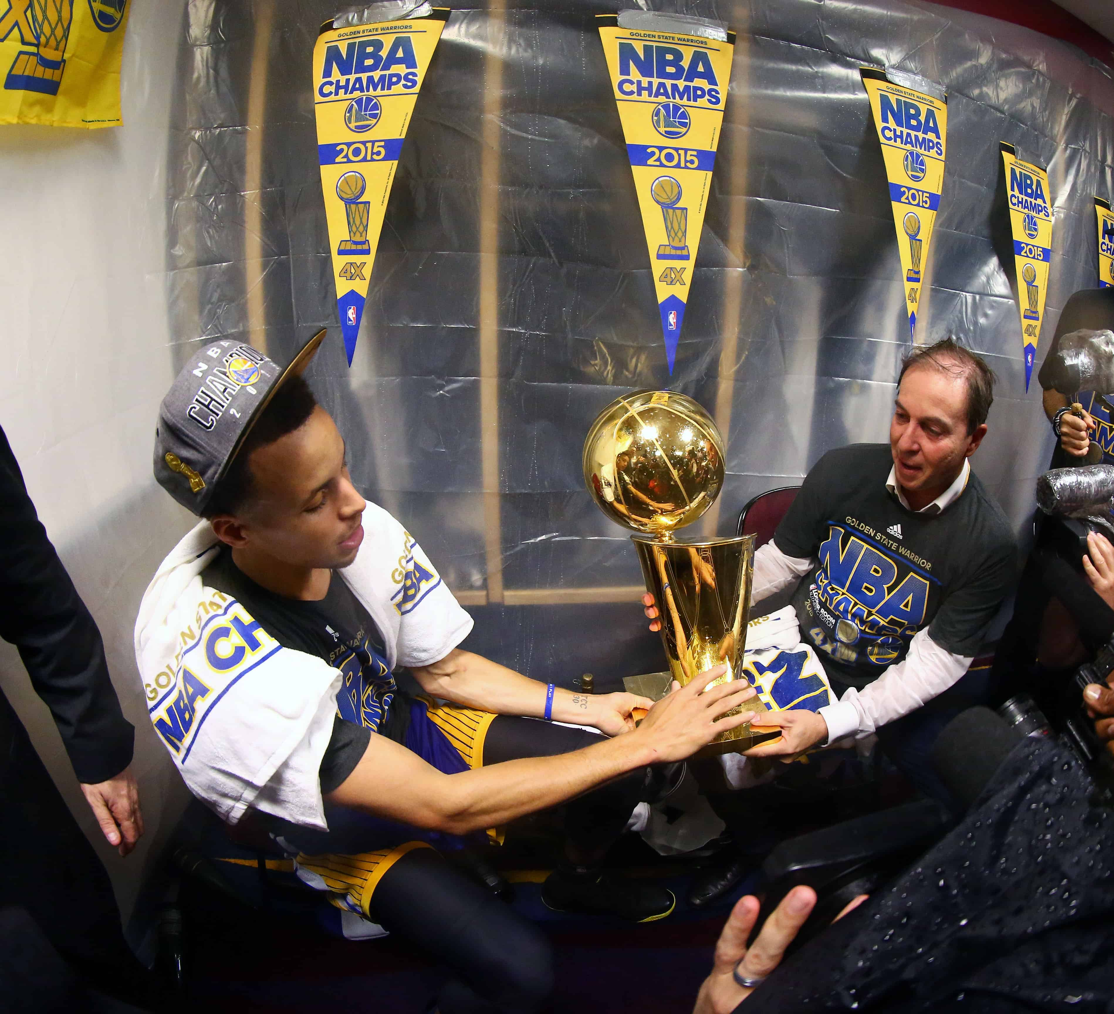 Stephen Curry (#30) of the Golden State Warriors smiles in the locker room as he hands majority owner Joseph Jacob the Larry O'Brien Championship Trophy.