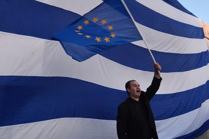A man waves a European flag in front of a giant Greek one.