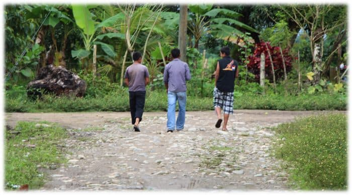 Three youth walk away from the grave of Gregorio Chávez near the community of La Panamá, Honduras, in 2013.