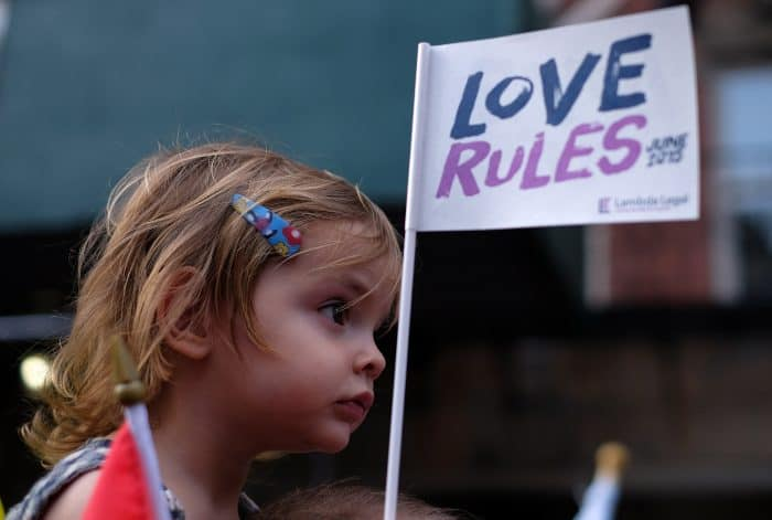 A child looks on as people celebrate the U.S. Supreme Court's historic decision.