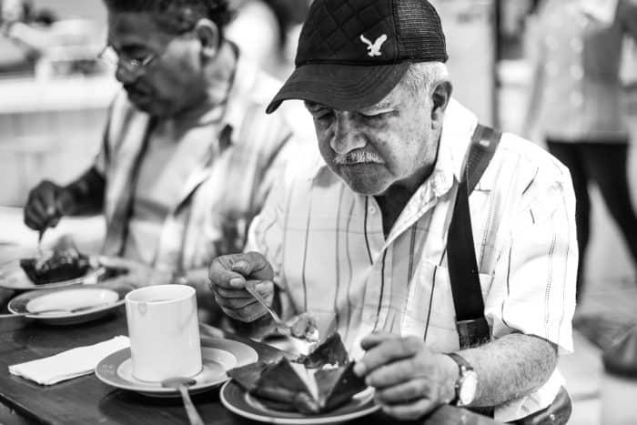 Rafael Chacón enjoys one of the 1000 tamales given by the organisation of the traditional Sagrado Corazón de Jesús mass in San José, July 25.