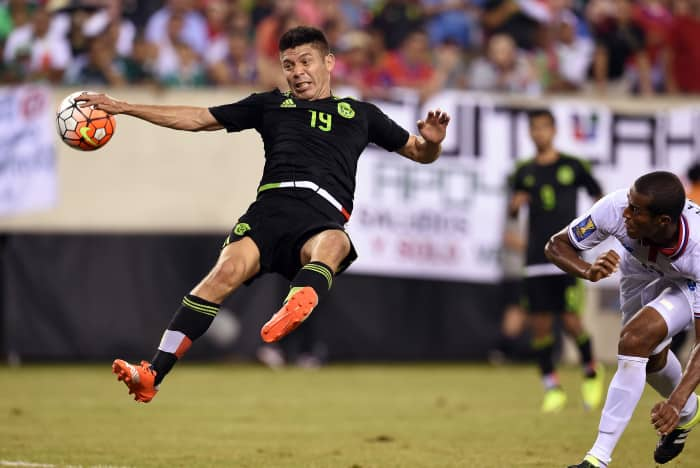 Mexico's forward Oribe Peralta (L) is challenged by Costa Rica's defender Roy Miller (R) which resulted a penalty kick against Costa Rica during their CONCACAF Gold Cup quarterfinals soccer match against Costa Rica at the MetLife Stadium in East Rutherford, New Jersey, on July 19, 2015. Mexico defeated Costa Rica 1-0.