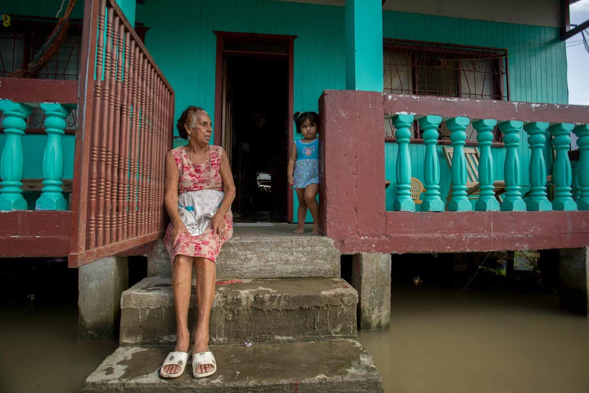 A young girl looks on in an area affected by flooding.