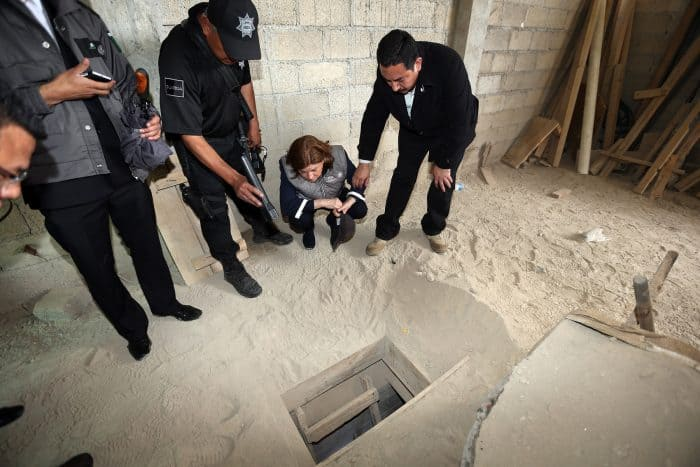 """Mexico's Attorney General, Arely Gómez (second from right), looks at the alleged end of the tunnel through which Mexican drug lord Joaquín """"El Chapo"""" Guzmán could have escaped from the Altiplano prison, at a house in Almoloya de Juárez, Mexico, on July 12, 2015."""
