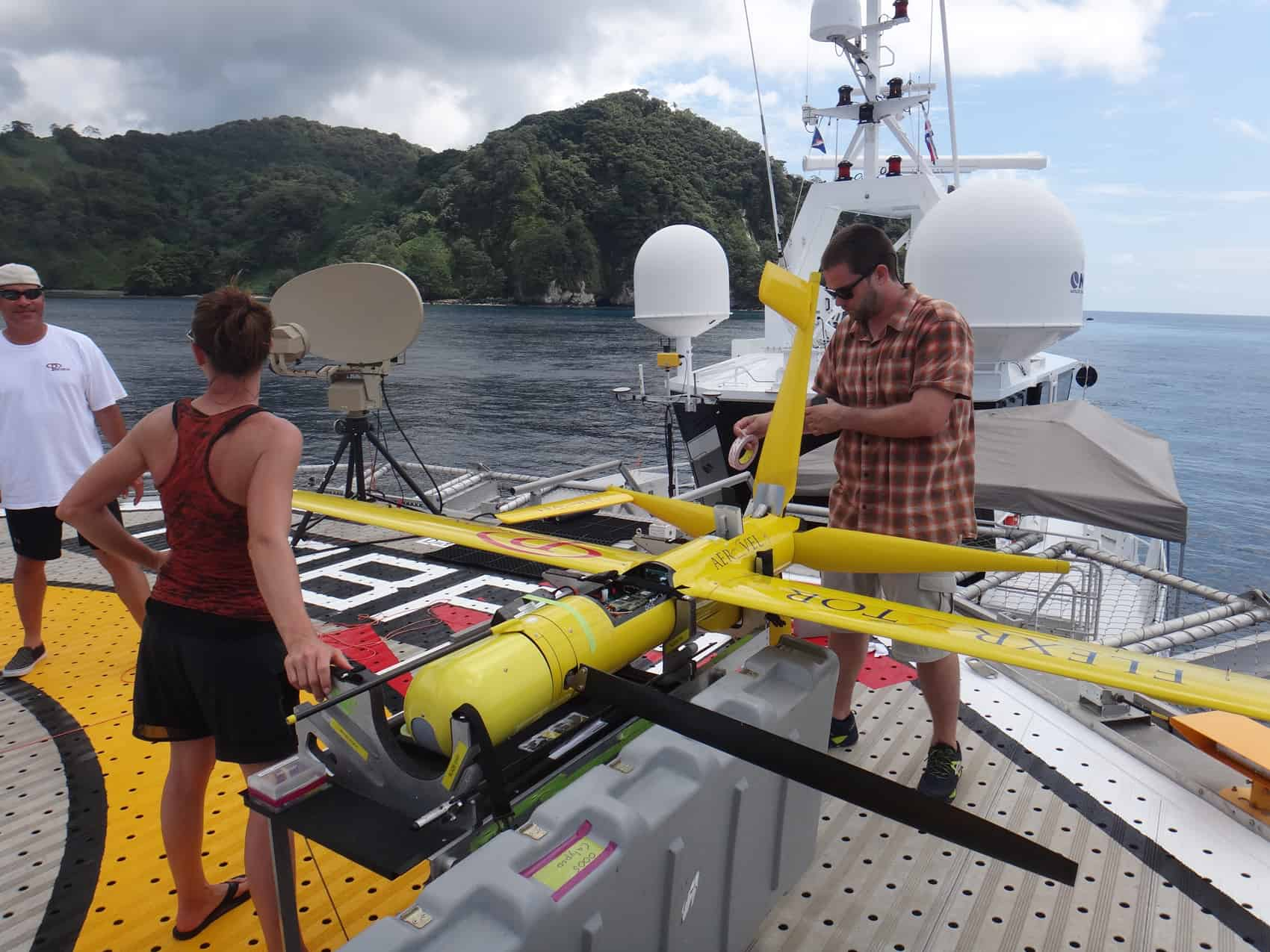 Charissa Moen of Precision Integrated and Andy Crafts of UAV manufacturer Aeroval inspect a Flexrotor drone during a test flight in Cocos Island in May, 2015.