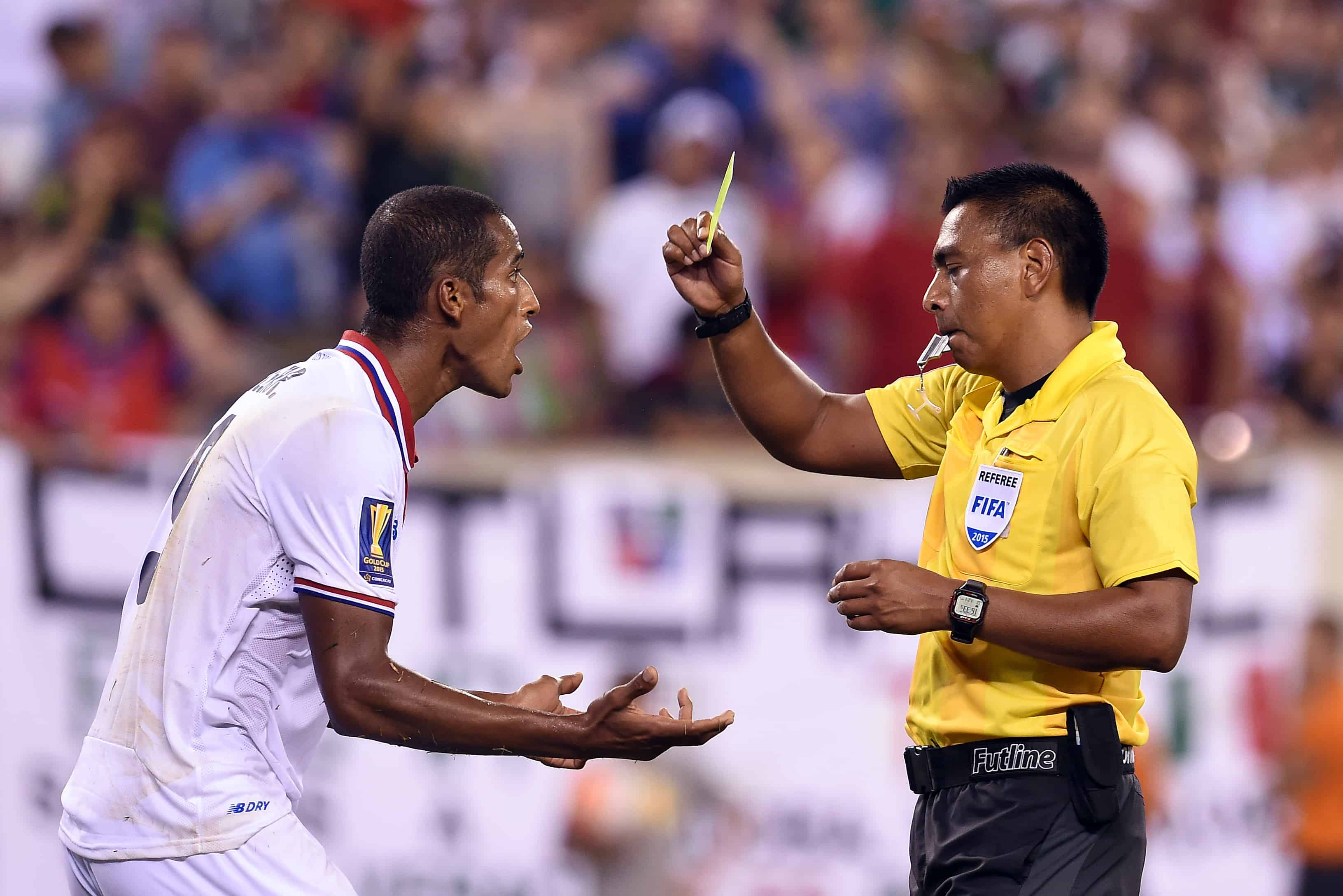 Costa Rica's defender Roy Miller (L) is given a yellow card by the referee during the CONCACAF Gold Cup quarterfinals soccer match against Mexico at the MetLife Stadium in East Rutherford, New Jersey, on July 19, 2015.