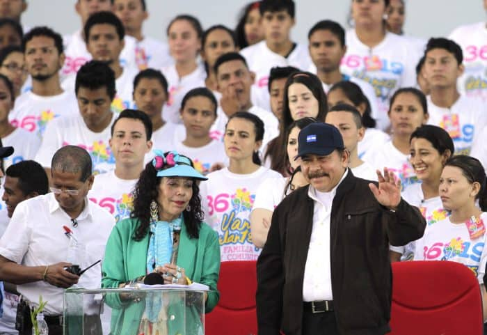 Nicaraguan President Daniel Ortega and First Lady Rosario Murillo wave to supporters during the celebration of the 36th anniversary of the Sandinista Revolution at La Fe square in Managua