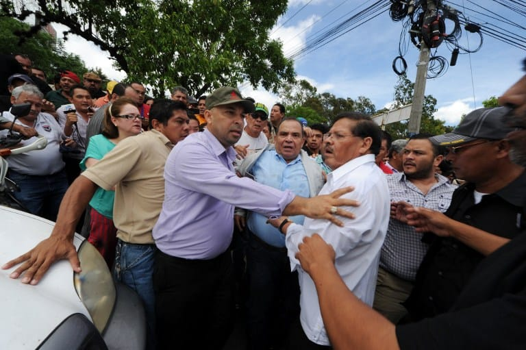 Supporters and members of the LIBRE Party leave the court taking away with them Honduran journalist David Romero (center), director of Radio Globo, in Tegucigalpa, on July 23, 2015. Romero, who has been denouncing corruption cases in the country, was facing charges of slander and defamation when his trial was suspended due to incidents in the vicinity of the court.