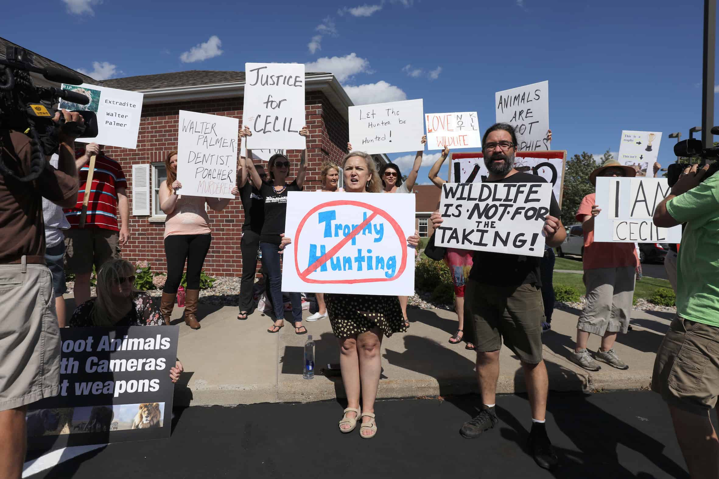 Protesters call attention to the alleged poaching of Cecil the lion in the parking lot of Dr. Walter Palmer's River Bluff Dental Clinic on July 29, 2015 in Bloomington, Minnesota.