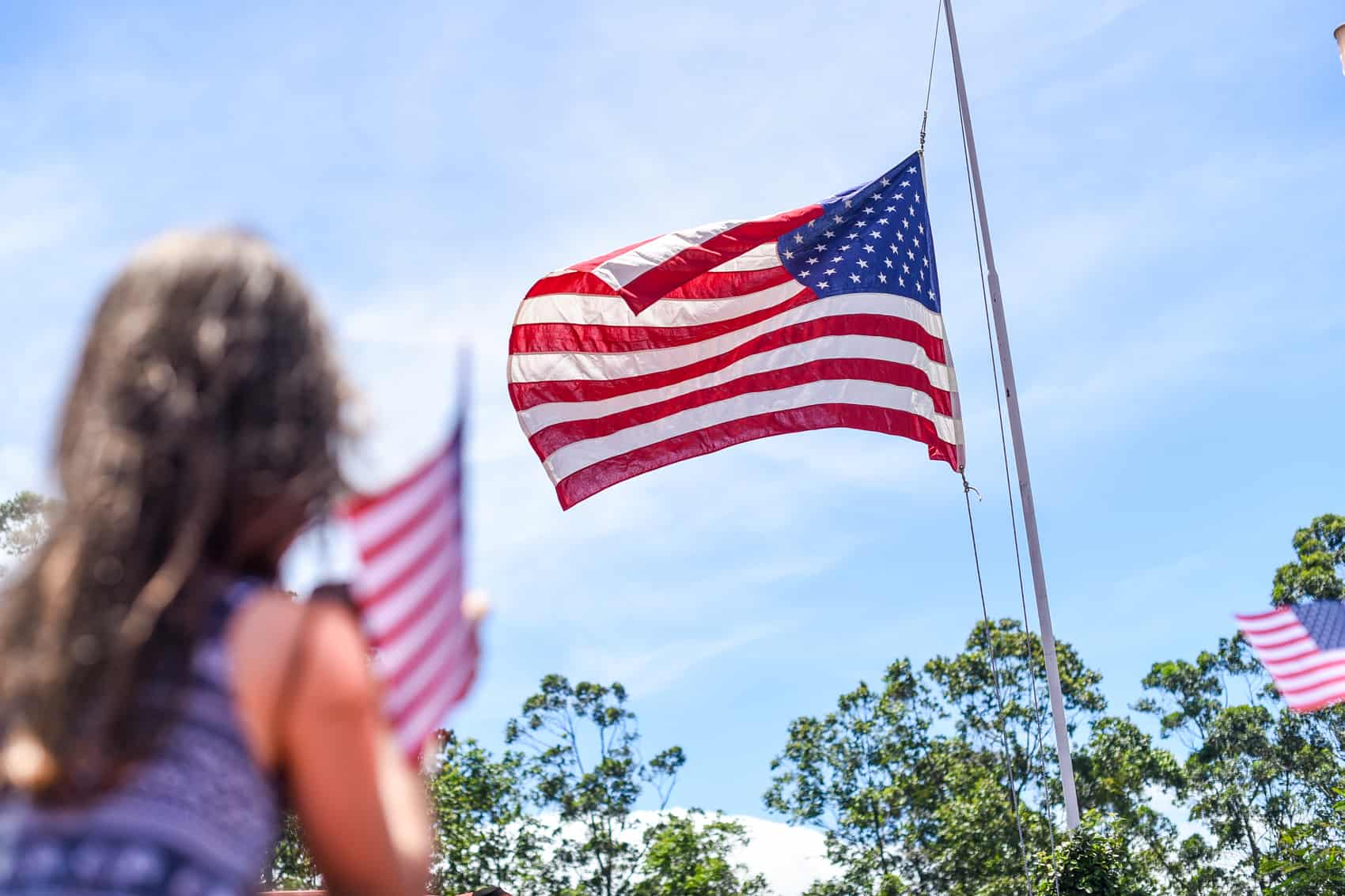 A girl looks on as the American flag ascends the flag pole.