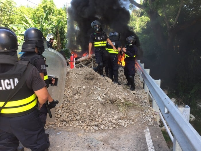 Police work to put out a fire set by strikers today in Paquera.