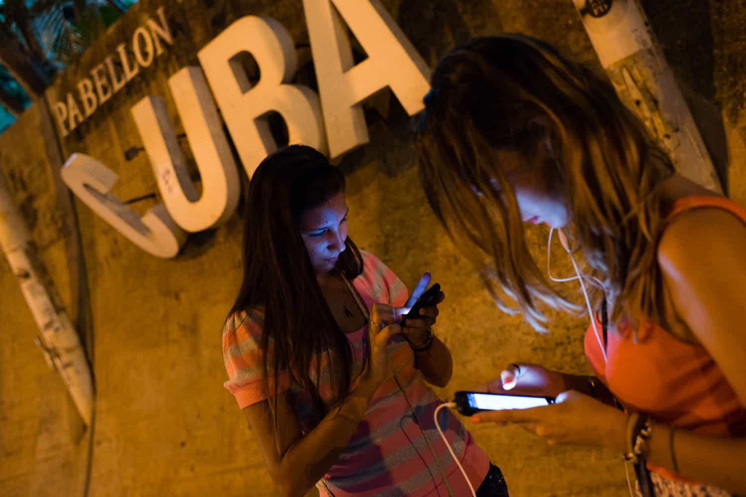 Using a new internet hotspot in Havana, Carolina Baez, 16, left, uses Facebook as her friend, Lara Gonzales, 16, video chats with an aunt in Miami on August 3. The recent addition of public WiFi hotspots has made the internet much more affordable in Cuba.