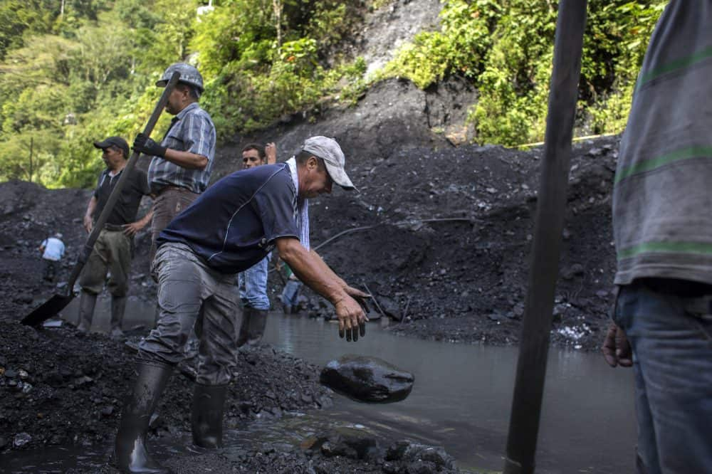 Emerald mine laborer José Vicente Ico, center, drops a rock while digging through mined rubble outside the Minería Texas Colombia plant in Muzo, Colombia, on July 26, 2015. Apart from the rare chance that they strike big, informal emerald miners usually make between $35 and $70 dollars a month.