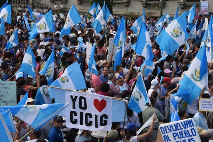 "Protesters wave Guatemalan flags and a sign reading ""I love CICIG."""