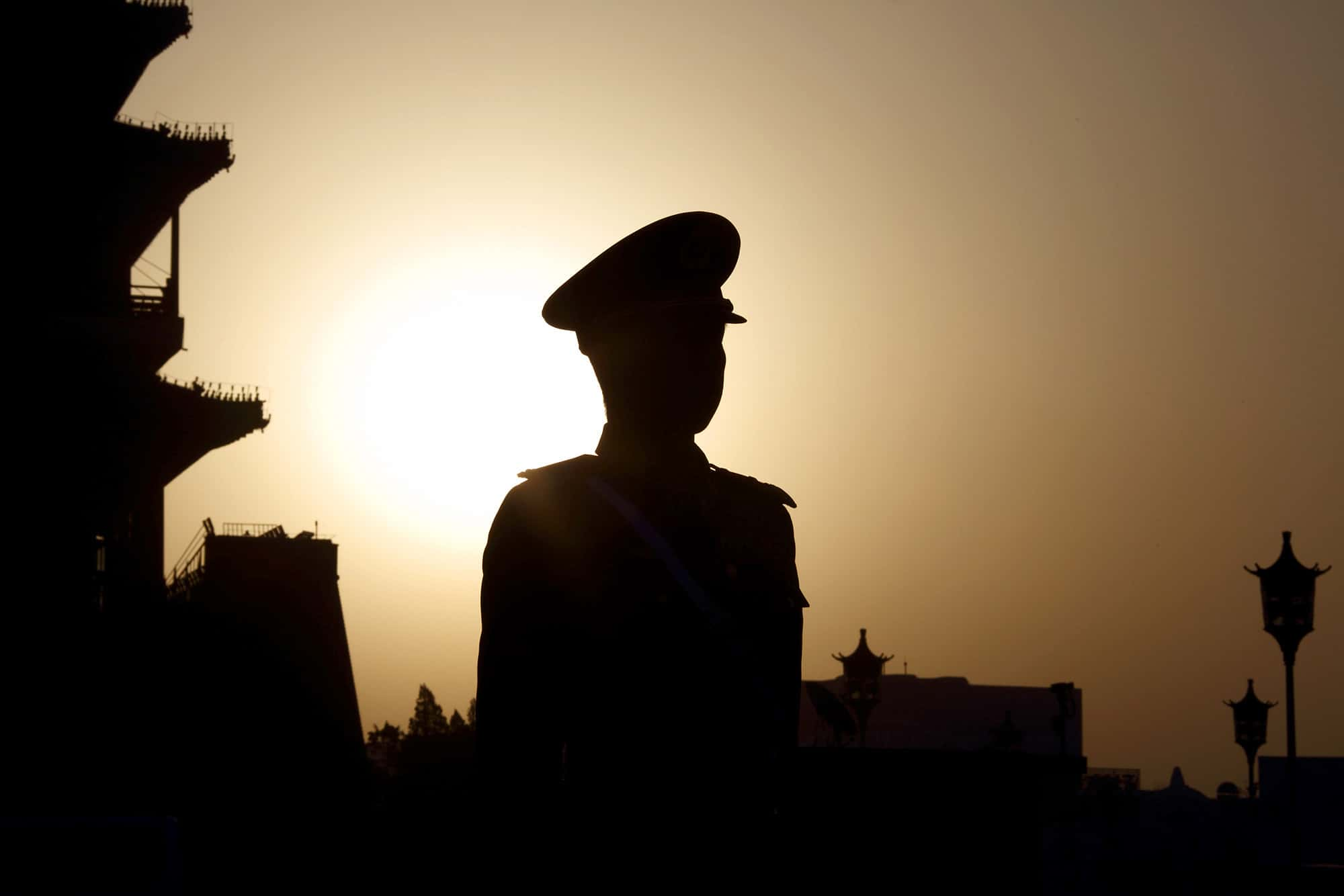 The sun rises behind a paramilitary police officer standing guard outside Tiananmen Square.