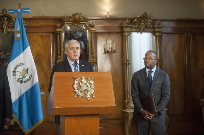 Molina, left, delivers a speech as U.S. Ambassador Todd Robinson looks on.