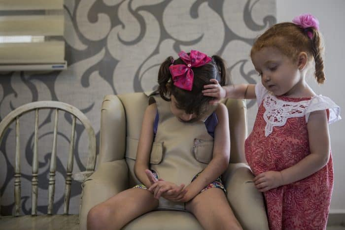 Valentina Elizalde, 2, right, comforts her sister Grace as she goes through one of her hourly convulsions in the living room of their home in Monterrey, Mexico, on August 12, 2015.