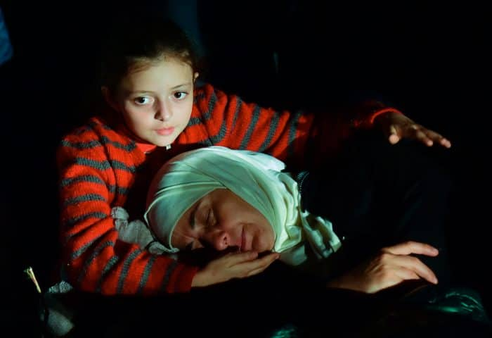 A migrant girl and her mother rest at the collector-point near Roszke village at the Hungarian-Serbian border.