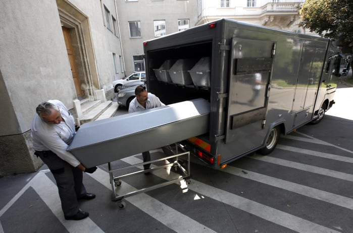 Ten coffins with the bodies of migrants who died in an abandoned lorry are unloaded from a van.