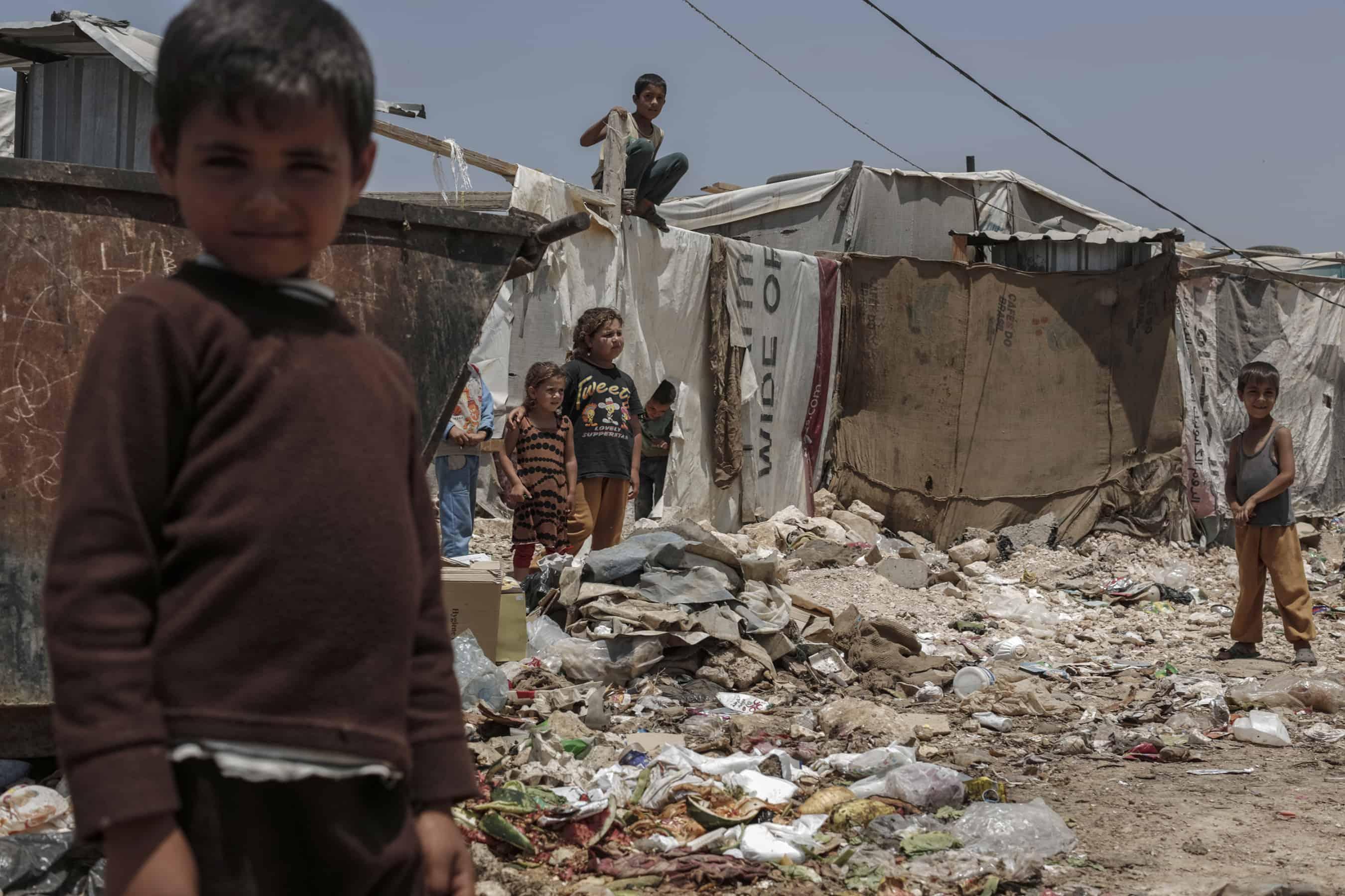 Children play amid garbage at an informal Syrian refugee settlement near Zahle, Lebanon.