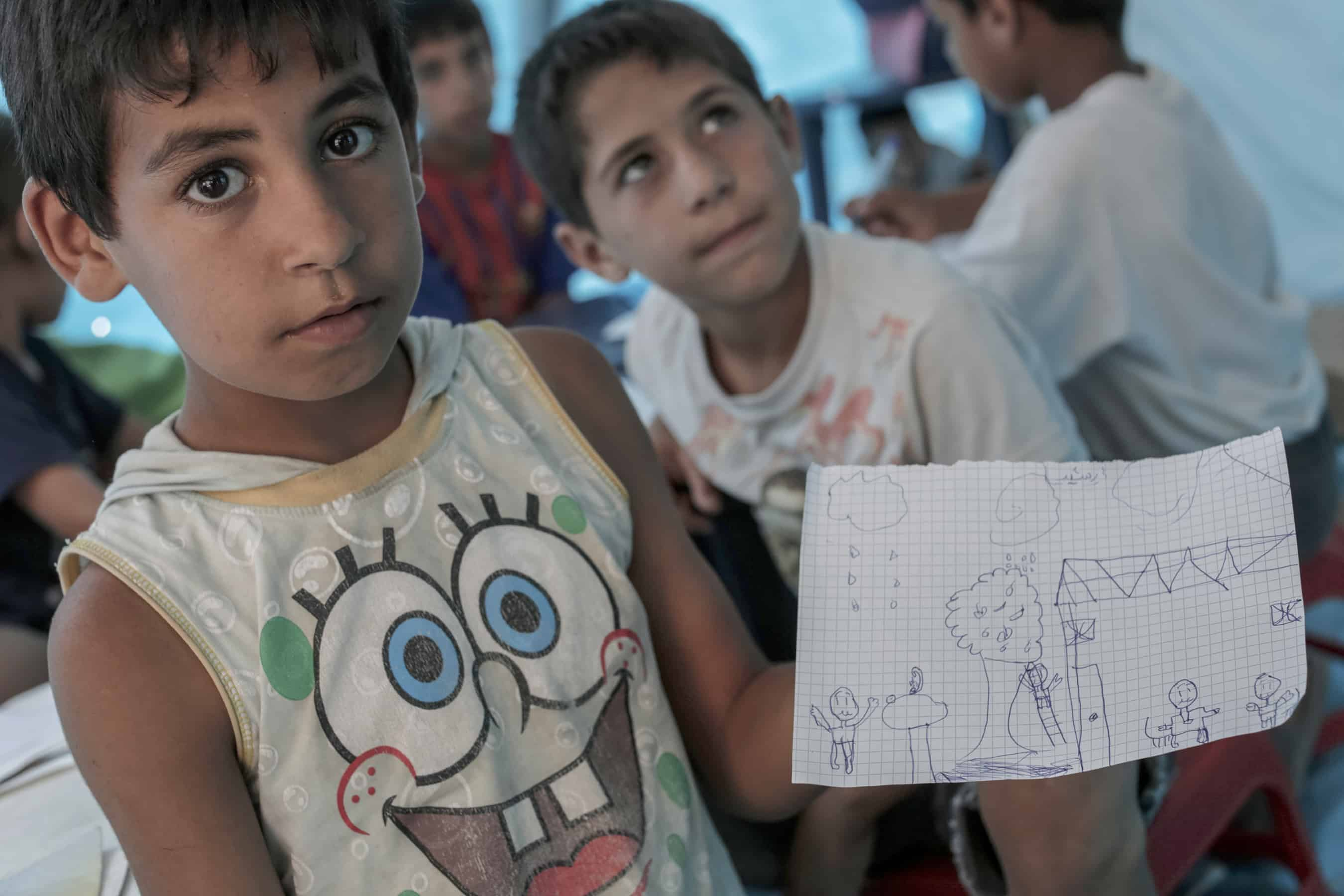 Rashid Hamadi, 9, holds a picture he drew at a school set up by a charity inside a Syrian refugee settlement in Al-Minya, Lebanon.