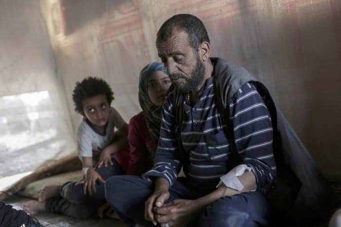 Faraj al-Ali, 43, who was left blind and suffering from kidney failure after being imprisoned by the Syrian regime in 2011, sits with his daughters.