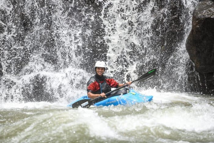 A kayaker at the base of a waterfall.