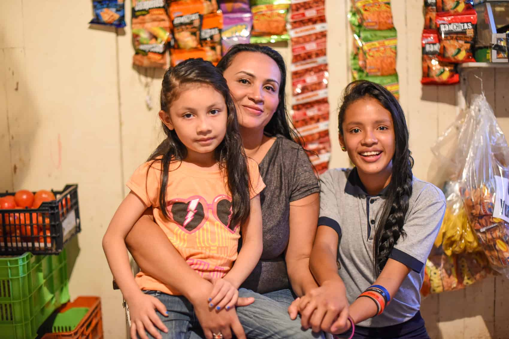 Zeneyda Flores with two of her four daughters, Liath (left) and Libby (right), in their home in Triángulo de la Solidaridad, August 13, 2015.
