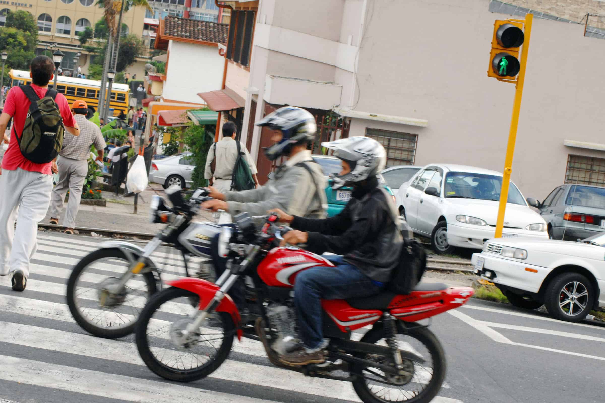 Motorcyclists run a red light in San José as pedestrians are in the crosswalk on Second Avenue near the National Museum.