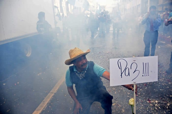 "A man holds a sign declaring ""Peace"" after the Guatemalan Congress voted unanimously to strip embattled President Otto Pérez Molina's immunity."