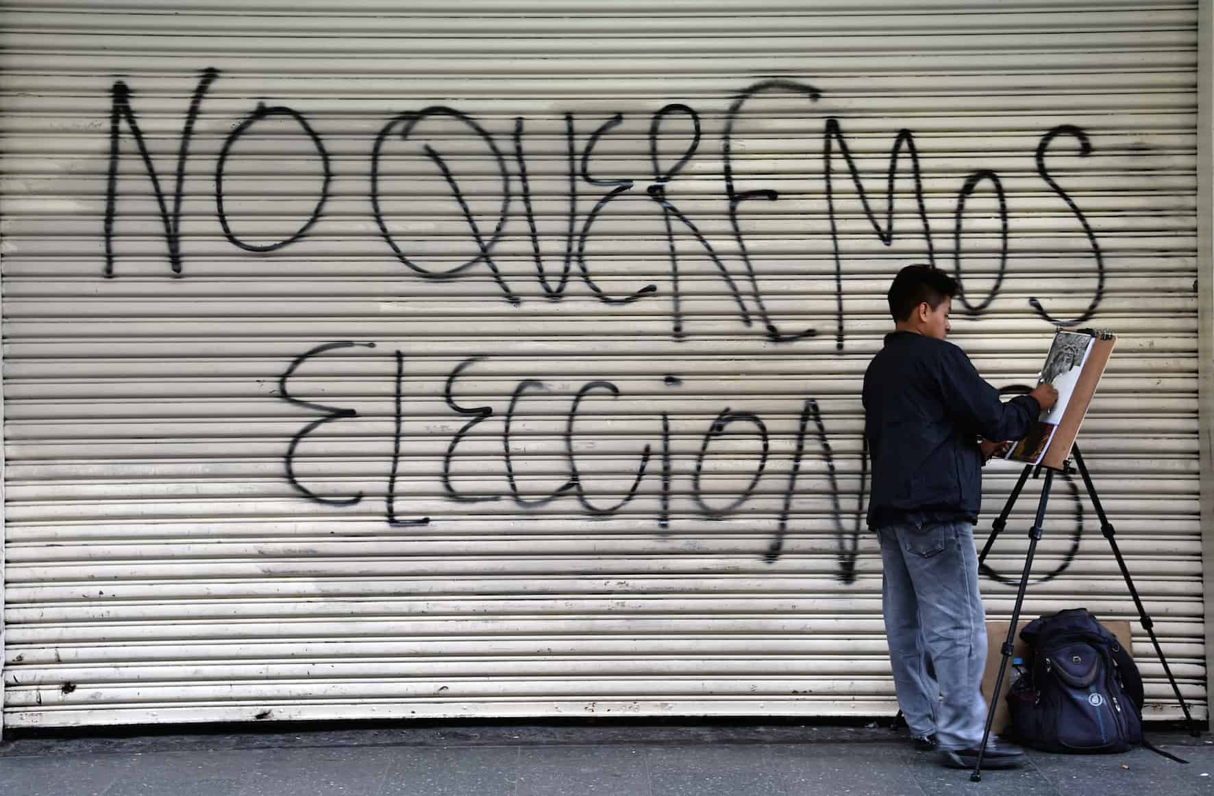 """A man paints next to a graffiti reading """"We don't want elections"""" on the eve of general elections in Guatemala City on Sept. 5, 2015. Guatemalans disgusted with rampant corruption that felled their president are set to vote Sunday in elections many see as meaningless without a vast political system cleanup."""