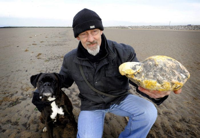 A photo from Jan. 28, 2013, in Morecambe, northwest England, shows Ken Wilman posing for pictures with his dog Madge and a yellowish stone which he hoped is a rare form of whale vomit, or ambergris.