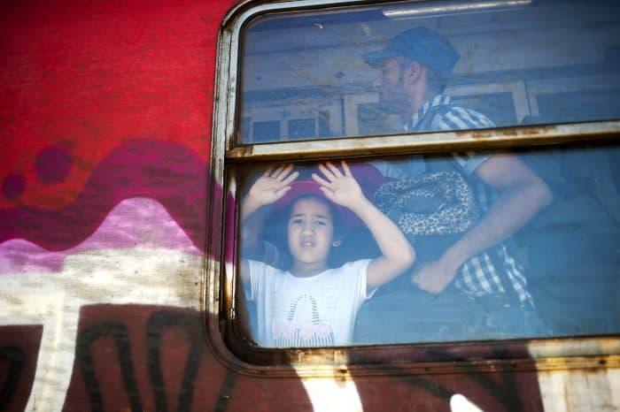 A boy looks through the window of a train.