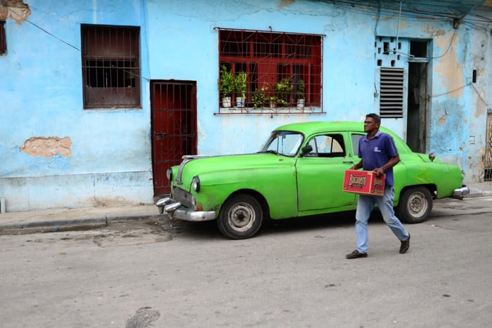 A man carries a case of beer through the streets of Havana.