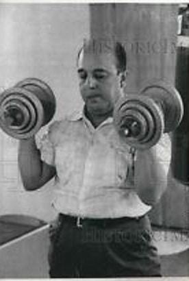 Venezuelan President Marcos Pérez Jiménez pumping iron.
