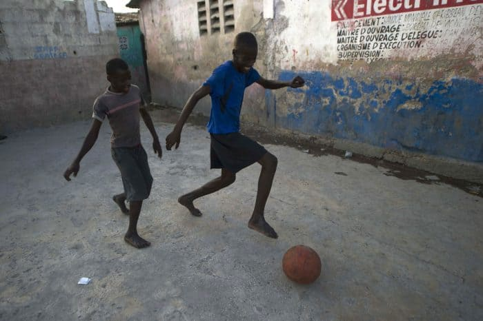 Haiti, boys playing football in Cite Soleil