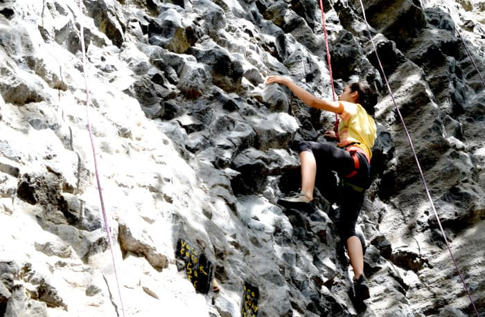 A rock climber scales a wall at Escalada Cachí, Cartago.
