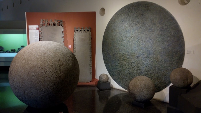 Stone spheres found in southwest Costa Rica, with a representation on the wall of the largest ever found.