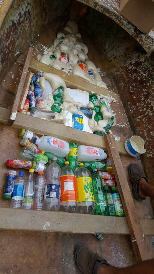 Empty bottles in boat, ready to be fixed in place with foam.