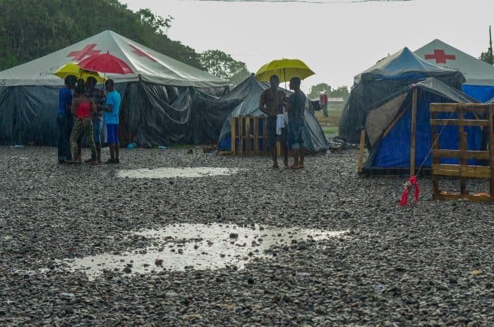 African migrants stand under umbrellas in a camp.