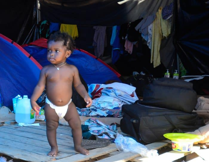 A baby in a diaper stands among tents and bags at the Paso Canoas border camp.