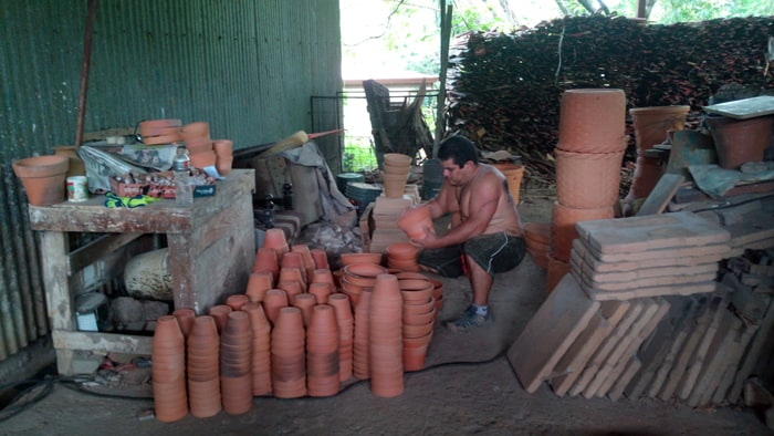 A worker taps new pots to make sure they aren't broken.