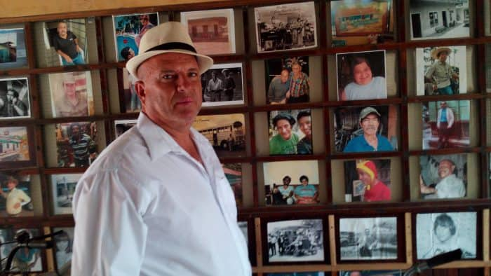 Héctor Aguilar in front of his photo wall at Antiguedades, his Santa Ana antiques shop.