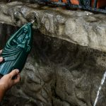 A pilgrim fills a bottle depicting Costa Rica's patron saint, La Negrita, with holy water.