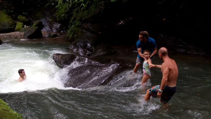 A father, a daughter and a couple of guides explore a waterfall at Punta Mala.
