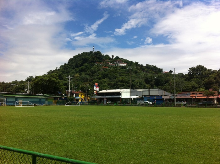 Soccer field in Quepos, with nice houses on the hills behind.