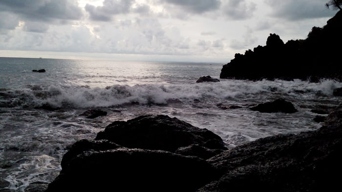 Waves crash on rocks as the day wanes.