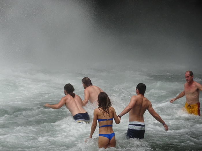 Braving the fierce currents at the base of La Fortuna Waterfall.