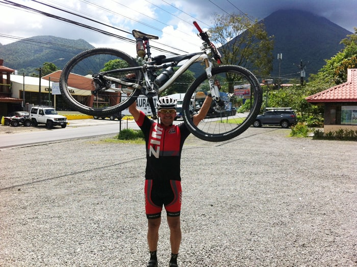 A San José cyclist celebrates in Fortuna after completing a circuit of Lake Arenal.