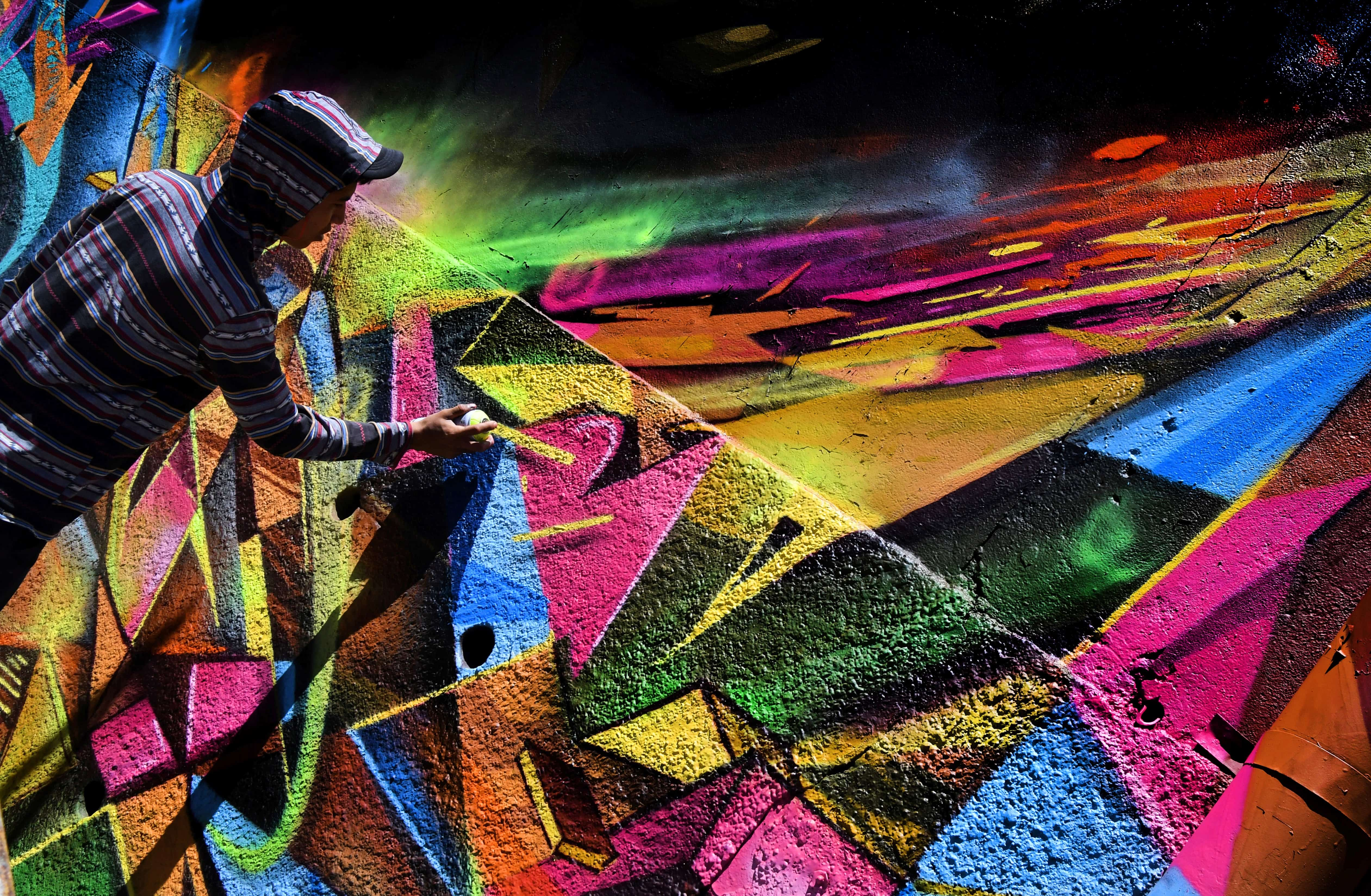An artist works on a mural during the Aliados Festival in San José, Costa Rica, on March 11, 2018.